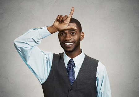 unprofessional: Closeup portrait smiling young man showing loser sign on forehead, looking at you with happiness at camera gesture, isolated black background. Human emotions, facial expressions, feelings, nature Stock Photo