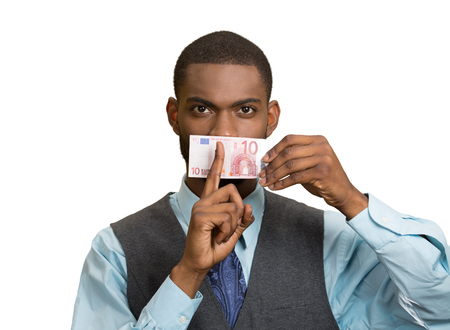 under paid: Closeup portrait handsome corrupt guy, businessman holding euro bill currency to mouth, showing shhh sign, isolated white background. Bribery concept in politics, business, diplomacy. Face expressions Stock Photo