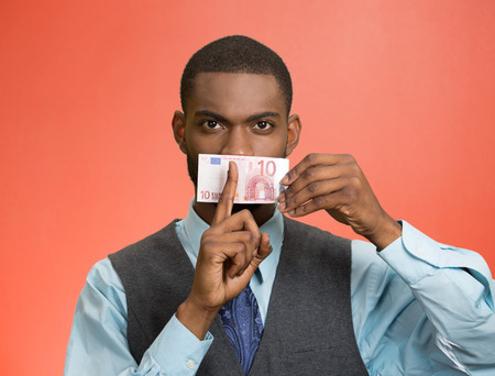 shhh: Closeup portrait handsome corrupt guy, businessman holding euro bill currency to mouth, showing shhh sign, isolated red background. Bribery concept in politics, business, diplomacy. Face expressions Stock Photo