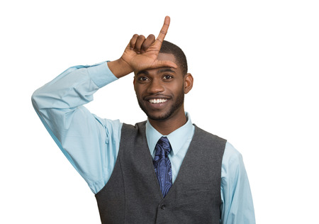 Closeup portrait smiling young man showing loser sign on forehead, looking at you with happiness at camera gesture, isolated white background. Human emotions, facial expressions, feelings, nature