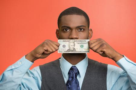no integrity: Closeup portrait handsome young corrupt corporate man in blue shirt holding twenty dollar bill to mouth, isolated red background. Bribery concept in politics, business, diplomacy. Life perception