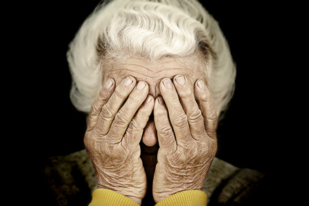 Closeup portrait sad depressed, stressed, thoughtful, senior, old woman, gloomy, worried, covering her face, isolated black background. Human face expressions, emotion, feelings, reaction, attitude Stock Photo