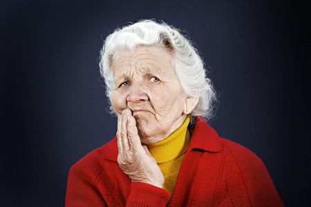 deliberation: Closeup portrait, senior, serious mature, older woman, looking at you camera gesture skeptically isolated black background. Negative human emotion facial expression, feeling, body language, perception Stock Photo