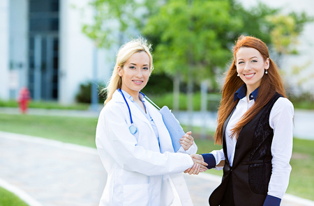frontiers: Closeup portrait happy, smiling health care professional, doctor, nurse shaking hands with satisfied female patient, isolated outdoors hospital background. Clinic care coverage, treatment plan concept