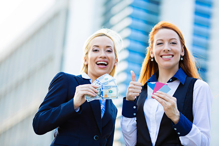 Closeup portrait two smiling business women with credit cards and cash on hands, convenience of electronic money isolated corporate office background. Financial decision, banking system concept