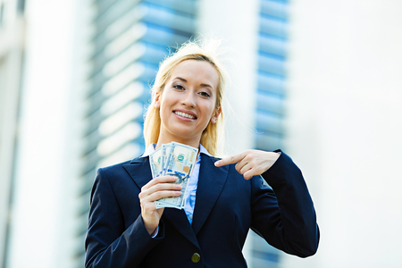 financial reward: Closeup portrait super happy excited successful young business woman holding money dollar bills in hand isolated corporate office background. Positive emotion face expression feeling. Financial reward