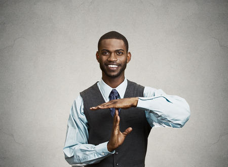 Closeup portrait young, happy, smiling, executive company man showing time out gesture with hands, isolated grey background. Positive human emotion, facial expression feeling, body language, attitude photo