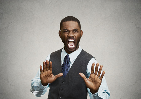 outrage: Closeup portrait furious angry annoyed displeased young man raising hands up to say no stop right there isolated grey background. Negative human emotion facial expression sign symbol body language