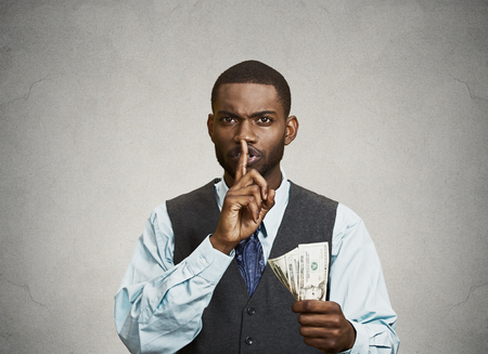 Closeup portrait handsome corrupt guy businessman holding dollar bill in hand showing shhh sign finger to lips isolated grey background. Bribery concept politics, business diplomacy. Face expression Stock Photo