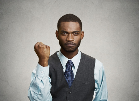 pissed: Closeup portrait angry cranky upset pissed off young man, worker business employee putting up fist ready to give knuckle sandwich isolated grey background. Negative emotion, facial expression, feeling Stock Photo