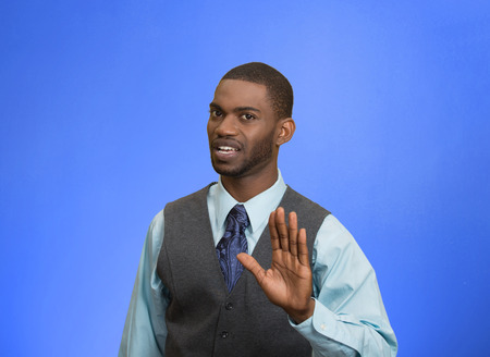 Closeup portrait furious angry annoyed displeased young man raising hands up to say no stop right there isolated blue background. Negative human emotion facial expression sign symbol body language Stock Photo