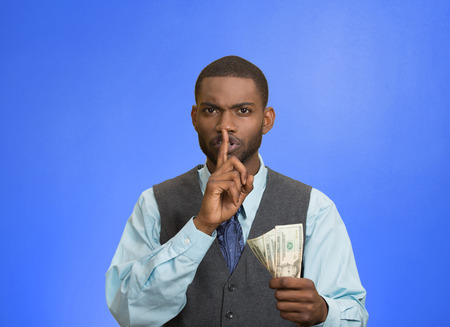 under paid: Closeup portrait handsome corrupt guy businessman holding dollar bill in hand showing shhh sign finger to lips isolated blue background. Bribery concept politics, business diplomacy. Face expression Stock Photo