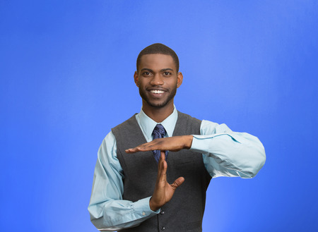 Closeup portrait young, happy, smiling, executive company man showing time out gesture with hands, isolated blue background. Positive human emotion, facial expression feelings, body language attitude photo