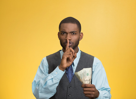 Closeup portrait handsome corrupt guy businessman holding dollar bill in hand showing shhh sign finger to lips isolated yellow background. Bribery concept politics, business diplomacy. Face expression