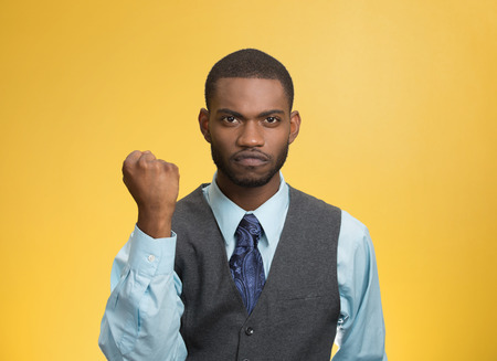 aggravated: Closeup portrait angry cranky upset pissed off young man, worker business employee putting up fist ready to give knuckle sandwich isolated yellow background. Negative emotion facial expression feeling