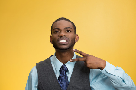 cut off head: Closeup portrait, angry, mad young executive man gesturing with hand to stop talking, cut it out, or he will take your head off isolated yellow background. Negative emotion, facial expression feelings