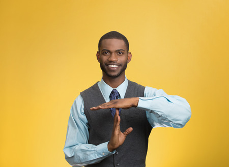 Closeup portrait young, happy, smiling, executive company man showing time out gesture with hands, isolated yellow background. Positive human emotion, facial expression feeling body language attitude photo