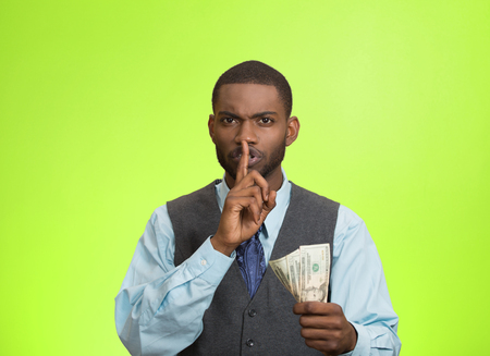 under paid: Closeup portrait handsome corrupt guy businessman holding dollar bill in hand showing shhh sign finger to lips isolated green background. Bribery concept politics, business diplomacy. Face expression
