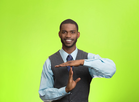 Closeup portrait young, happy, smiling, executive company man showing time out gesture with hands, isolated green background. Positive human emotion, facial expression feelings, body language attitude photo