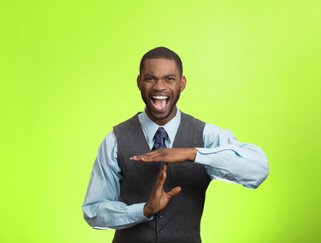 aggravated: Closeup portrait stressed angry young business man showing time out gesture with hands, isolated green background. Negative human emotions, facial expressions, sign, symbols, body language, attitude