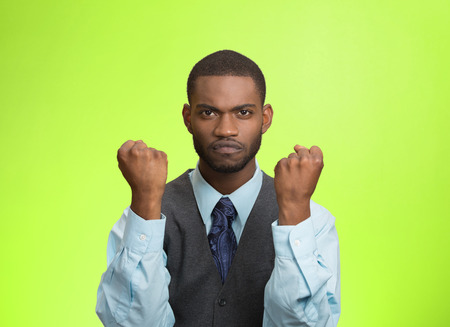 aggravated: Closeup portrait angry cranky upset pissed off young man, worker business employee putting up fist ready to give knuckle sandwich isolated green background. Negative emotion, facial expression feeling