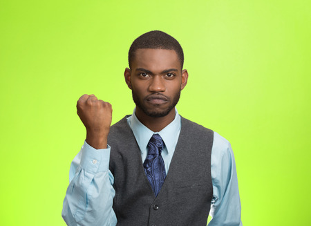 pissed: Closeup portrait angry cranky upset pissed off young man, worker business employee putting up fist ready to give knuckle sandwich isolated green background. Negative emotion, facial expression feeling