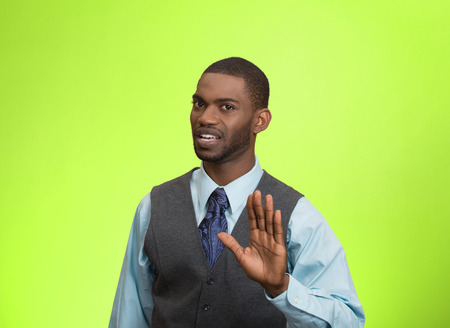 irate: Closeup portrait furious angry annoyed displeased young man raising hands up to say no stop right there isolated green background. Negative human emotion facial expression sign symbol body language Stock Photo