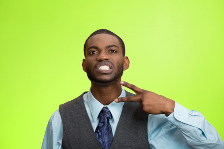 cut off head: Closeup portrait, angry, mad young executive man gesturing with hand to stop talking, cut it out, or he will take your head off, isolated green background. Negative emotion, facial expression feelings