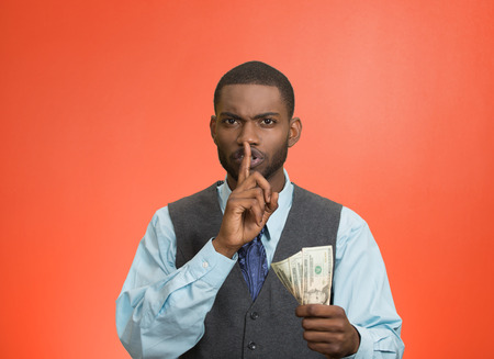 bribery: Closeup portrait handsome corrupt guy businessman holding dollar bill in hand showing shhh sign finger to lips isolated red background. Bribery concept politics, business diplomacy. Face expression Stock Photo