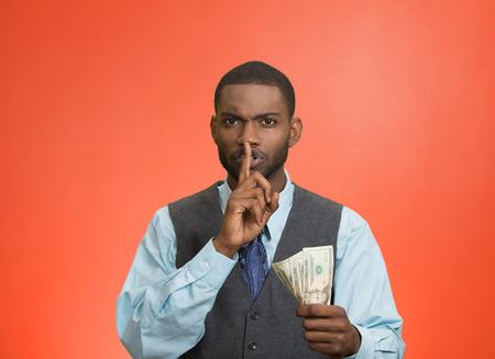 Retrato del primer chico apuesto hombre de negocios corrupto sosteniendo el billete de dólar en la mano que muestra shhh signo de dedo en los labios aislados en fondo rojo. La política del concepto de soborno, diplomacia empresarial. Expresión de la cara Foto de archivo