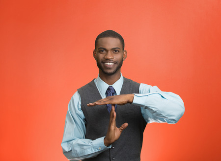Closeup portrait young, happy, smiling, executive company man showing time out gesture with hands, isolated red background. Positive human emotion, facial expression feelings, body language, attitude photo