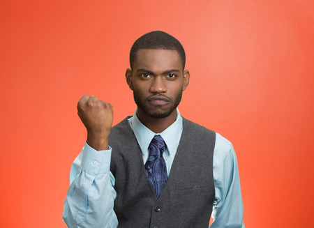 cranky: Closeup portrait angry cranky, upset, pissed off young man, worker, business employee putting up fist ready to give knuckle sandwich isolated red background. Negative emotion facial expression feeling Stock Photo