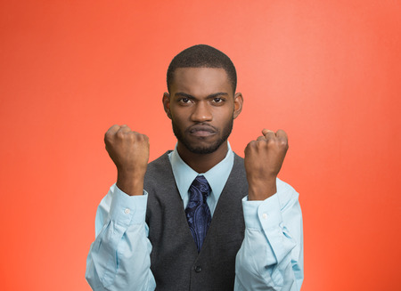 pissed: Closeup portrait angry cranky, upset, pissed off young man, worker, business employee putting up fist ready to give knuckle sandwich isolated red background. Negative emotion facial expression feeling Stock Photo