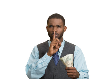 under paid: Closeup portrait handsome corrupt guy businessman holding dollar bill in hand showing shhh sign finger to lips isolated white background. Bribery concept politics, business diplomacy. Face expression Stock Photo