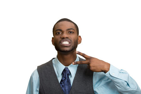 cut off head: Closeup portrait, angry, mad young executive man gesturing with hand to stop talking, cut it out, or he will take your head off isolated white background. Negative emotion, facial expression feelings Stock Photo