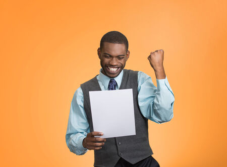 refinance: Closeup portrait happy excited young business man executive looking monthly statement glad to pay off bills isolated orange background. Positive emotion facial expression. Financial success good news Stock Photo