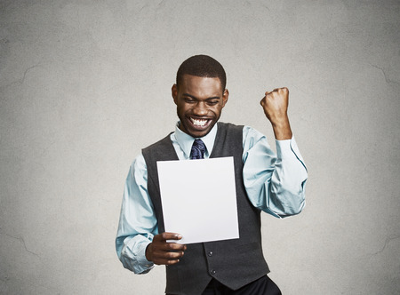 Closeup portrait happy excited young business man executive looking monthly statement glad to pay off bills isolated grey background. Positive emotion facial expression. Financial success good news Standard-Bild