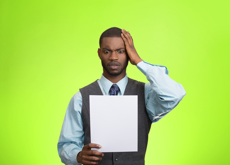 bank records: Closeup portrait shocked, funny looking young man, disgusted at monthly statement, test, application, results isolated green background. Negative human emotion, facial expression, feeling. Bad news