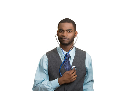 selfcontrol: Closeup portrait serious executive man, business person, worker listening to his heart with stethoscope isolated white background. Preventive medicine, financial condition concept. face expressions
