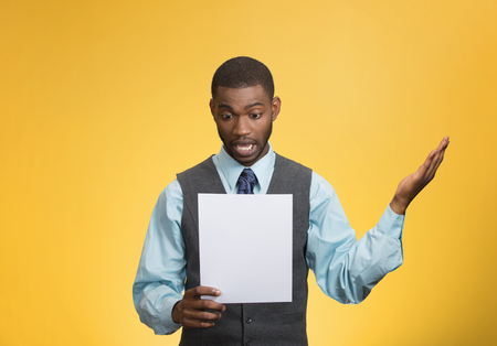 bank records: Closeup portrait shocked, funny looking young man, disgusted at monthly statement, test, application, results isolated yellow background. Negative human emotion, facial expression, feeling. Bad news Stock Photo