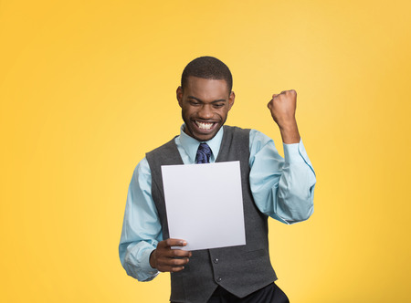 to raise: Closeup portrait happy excited young business man executive looking monthly statement glad to pay off bills isolated yellow background. Positive emotion facial expression. Financial success good news Stock Photo