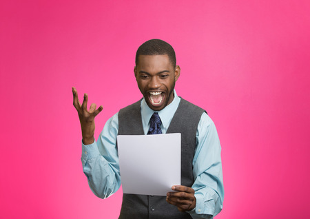 Closeup portrait happy excited young business man executive looking monthly statement glad to pay off bills isolated pink background. Positive emotion facial expression. Financial success good news photo