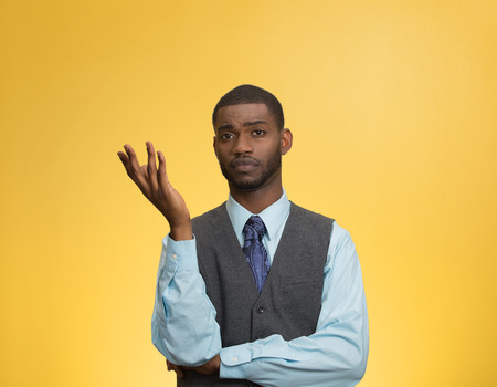 indifferent: Closeup portrait dumb clueless young executive man, arm out asking why what problem so who cares, I dont know, isolated yellow color background. Negative human emotion facial expression feelings Stock Photo