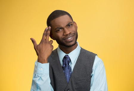 bonkers: Closeup portrait rude, difficult, angry young executive businessman gesturing with fingers against temple, are you crazy? Isolated yellow background. Negative human emotion, facial expression, feelings