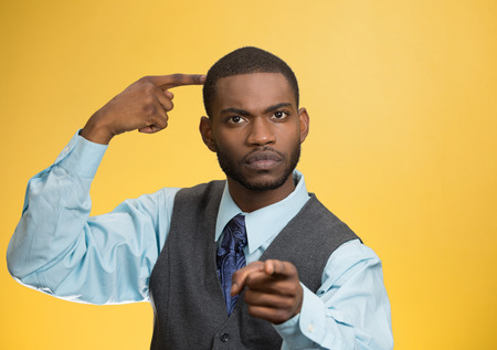 Closeup portrait rude, difficult, angry young executive businessman gesturing with fingers against temple, are you crazy? Isolated yellow background. Negative human emotion, facial expression, feelings