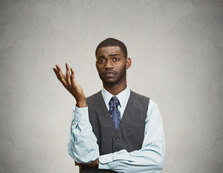 Closeup portrait dumb clueless young executive man, arm out asking why what problem so who cares, I don't know, isolated grey color background. Negative human emotion facial expression feelings Stock Photo