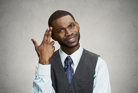 bonkers: Closeup portrait rude, difficult, angry young executive businessman gesturing with fingers against temple, are you crazy? Isolated grey background. Negative human emotion, facial expression, feelings