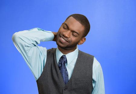 crick: Ritratto del primo piano, giovane dirigente con dolore spinale collo vertebra toracica dopo lunghe ore di lavoro, lo studio, isolato sfondo blu. Mancanza di supporto ergonomico. Faccia espressione, sentimenti