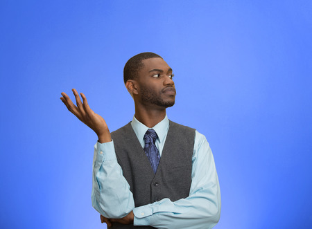 disregard: Closeup portrait dumb clueless young executive man, arm out asking why what problem so who cares, I dont know, isolated blue color background. Negative human emotion facial expression feelings