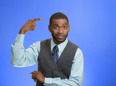 Closeup portrait rude, difficult angry young executive businessman gesturing with fingers against temple are you crazy? Isolated blue color background. Negative human emotion facial expression feeling